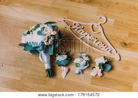 The composition of the bouquets of flowers and wooden sign bride lying on the floor
