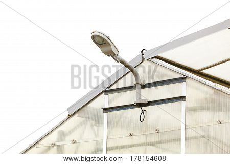 Light luminosity details in architecture concept. Lamp on transparent greenhouse with white sky background.