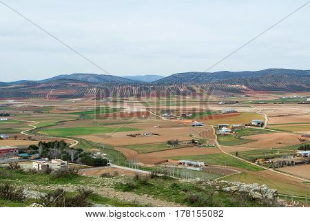A view from observation deck to fields farms and mountains near Consuegra town at spring cloudy day Castilla La Mancha Spain.