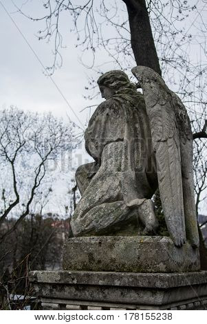 LVIV UKRAINE - JANUARY 6 2014: An old monument of angel at Lychakiv cemetery (Lviv Ukraine) on winter cloudy day.