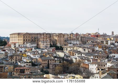 A view of Toledo old town medieval buildings with tile roofs churches and a building of Seminario Conciliar San Ildefonso.