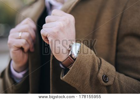 Luxury expensive fashion watch wealthy men in brown coat