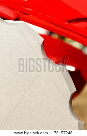 Industrial machinery workshop equipment concept. Detailed closeup of grey cutting disc on red machine.