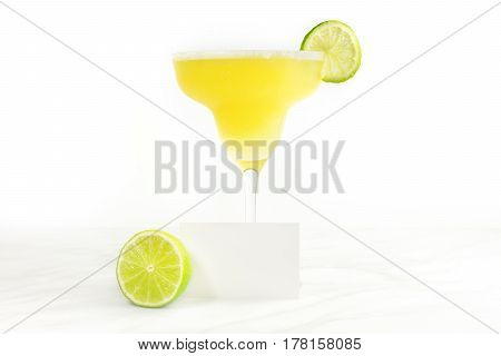Lemon Margarita cocktail with a wedge of lime and a blank card for copy space