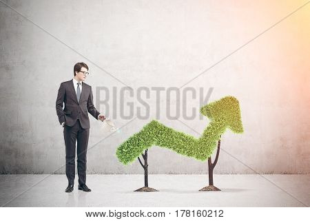 Portrait of a buisnessman standing near a graph made of grass in a city. Mock up