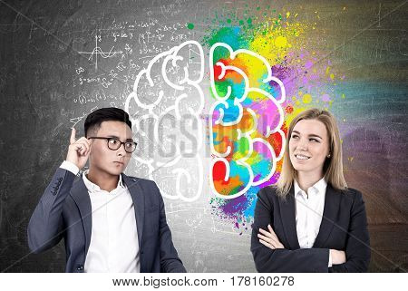 Portrait of an Asain businessman and a blond woman standing near a blackboard with a colorful brain sketch drawn on it.