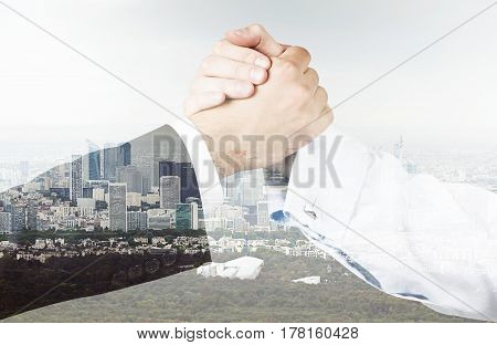 Close up of two businessmen shaking hands while standing against a city panorama. Double exposure.