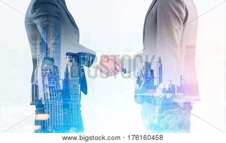 Close up of two businessmen shaking hands while standing against a blue city background. Toned image. Double exposure
