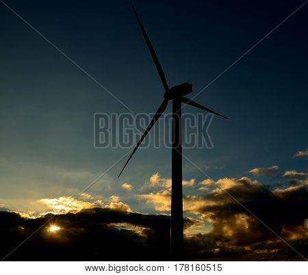 Wind turbine backlit with low clouds background at sunrise