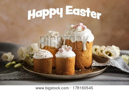 Tray with sweet cakes on wooden table. Text HAPPY EASTER on background