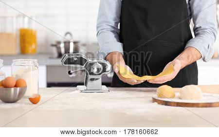 Man with pasta machine on table at kitchen