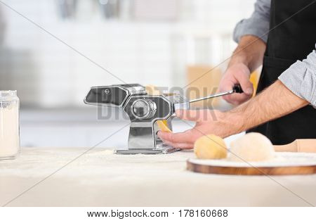 Man rolling dough for pasta on table, closeup