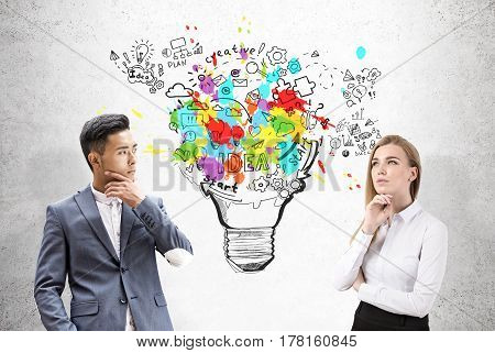 Portrait of an Asian businessman and a blond businesswoman standing near a oconcrete wall with a large and colorful light bulb sketch.