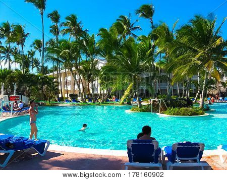 Punta Cana, Dominican republic - February 02, 2013: Ordinary tourists resting in VIK Arena Blanca hotel with pool under palms near the beach