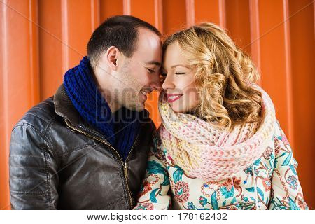 Happy couple smiling at each other on an orange background