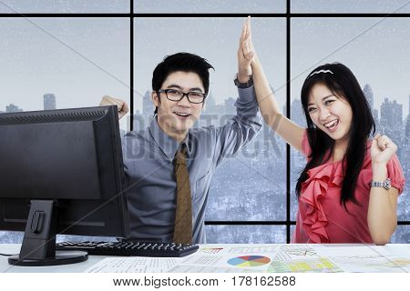 Image of two Asian employees celebrating their victory by clapping hands in the office with winter background on the window