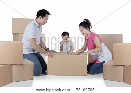 Image of Asian family is packing cardboard while moving into a new home isolated on white background