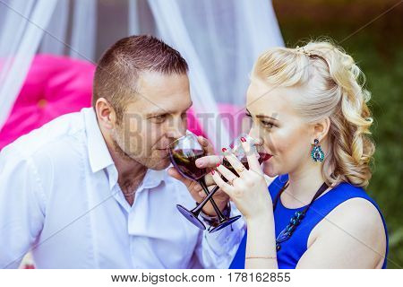 Man and woman sitting on the bed in the lawn and drinking wine from glasses and look at each other in Lviv, Ukraine.