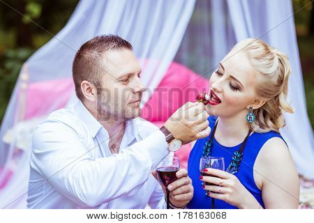 Man and woman sitting on the bed in the lawn with glasses of wine and woman eating strawberries from a man's hand in Lviv, Ukraine.