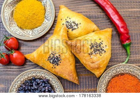 National Uzbek samsa dishes tomatoes red pepper and condiments on a brown wooden table