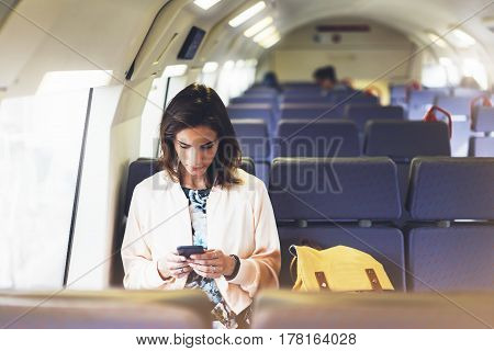 Enjoying travel. Young pretty woman traveling by train sitting near the window using smartphone and looking map. Tourist texting online message and plan route of railway railroad transport concept