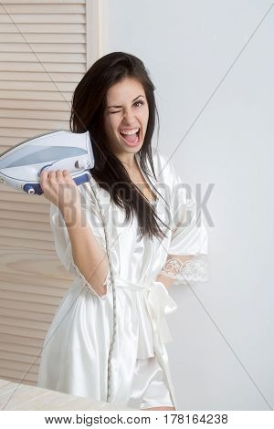 Happy pretty girl or beautiful woman housewife with long brunette hair in sexy dressing gown smiling with electric iron in hand indoors on white wall background. Housework and housekeeping
