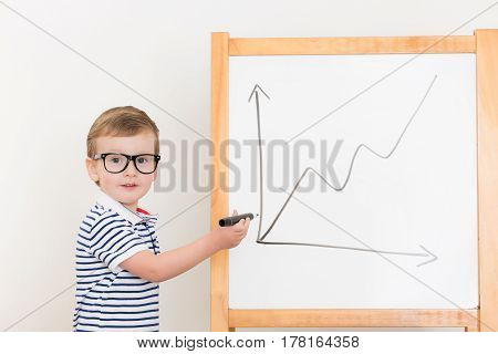 boy drawing graph on the board by marker
