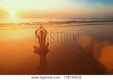 Sunset yoga woman meditation on Ocean coast.