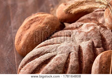 Different bread with buns and ears on wooden background. Close-up. Natural products and materials. Baker and tasty. Delicious food. Bread and baked goods on the brown background.