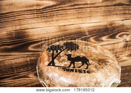 leather hand drum with the inscription Tunisia wooden background