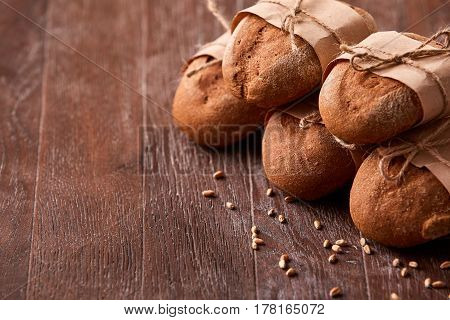 different bread on the wooden table, wheat, paper bags, rope. Brown background. Delicious food. Fresh baking. Tasty and appetizing. Angle position.