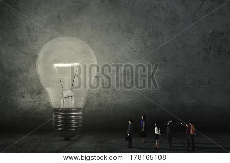 Group of little businesspeople looking at a big bright light bulb. Concept of a big and bright idea