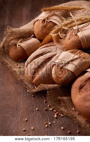 Fresh rye bread on the wooden table, wheat, paper bags, ears of wheat, rope and burlap. Vertical photo. Brown background. Delicious food. Fresh baking. Tasty and appetizing. Angle position.