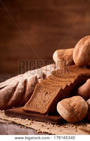 Freshly baked bread loaves on burlap on wooden table with brown blurred background. Texture closeup bakery products. Wheat. Slice of bread on the board. Vertical photo.