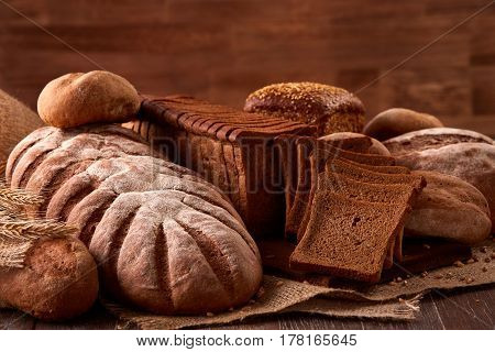 Different kinds of bread on burlap on the wooden table with blurred brown background. Kitchen or bakery poster design. With wheat and ears of wheat. Slice of the braed on the board. Tasty food.