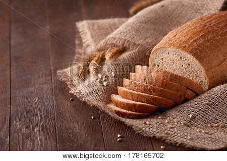Slices of bread on burlap on the dark wooden table, Space for text. With wheat and ears of wheat. Delicious food. Fresh baking. Tasty and appetizing.