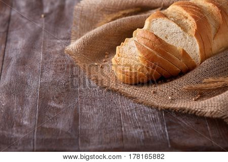 Slices of white bread on burlap on the dark wooden table, Space for text. With wheat and ears of wheat. Delicious food. Fresh baking. Tasty and appetizing. With flour.