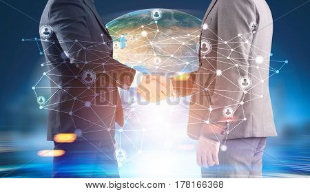 Two men are shaking hands while standing against an Earth image and a network sketch. Toned image double exposure