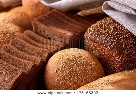Assortement of Freshly baked traditional bread with ears of wheat and white cloth. Sliceas of the bread and rulls. Background of bread. Delicious food. Fresh baking. Tasty and appetizing.