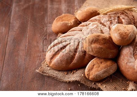 handmade tasty bread lying on burlap on the wooden table with flour, wheat and ears of wheat. Brown bread and rulls. Delicious food. Fresh baking. Tasty and appetizing.