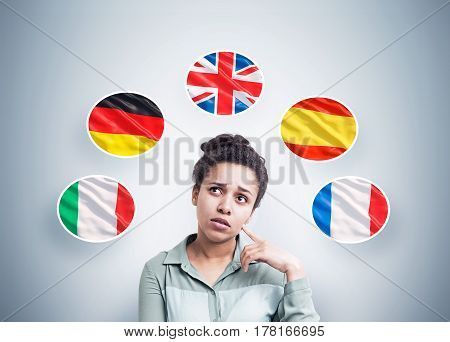 Portrait of a pensive African American woman standing near a gray wall with and five national flags around her.