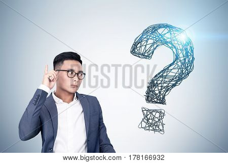 Portrait of an Asian buisnessman wearing glasses and standing near a gray wall with a shining question mark drawn on it.