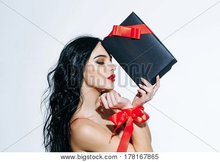 pretty woman or cute sexy girl in erotic bra with long curly brunette hair has red lips makeup on adorable face and ribbon bow on hands holds black present box isolated on white background