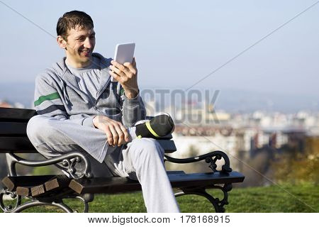 The smiling man is enjoying with digital tablet outdoors on the bench.