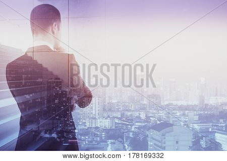 Back view of thoughtful man with stairs on city background. Success and growth concept. Double exposure
