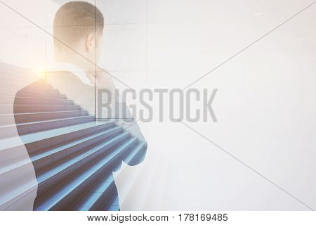 Back view of thoughtful male with stairs on city background. Success and growth concept. Double exposure
