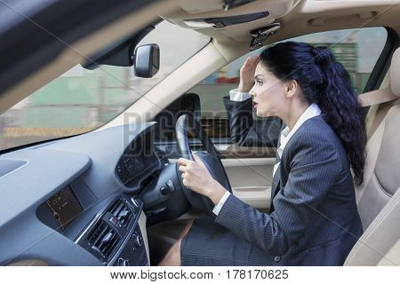 Portrait of Indian businesswoman looks hurry driving a car while looking at the road with container on the background on the window