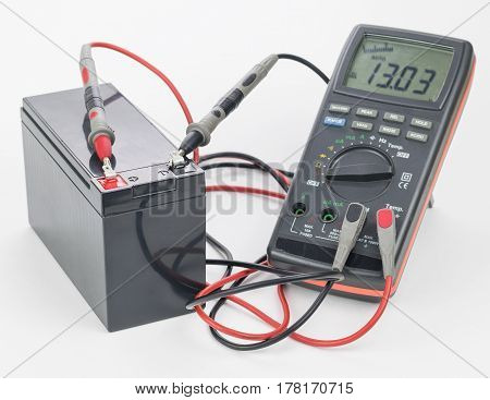 The battery is connected with a digital meter on a white background. The concept of clean energy.