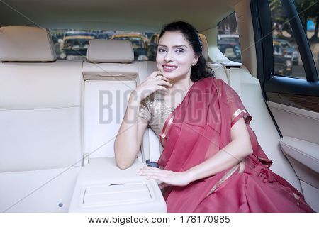 Portrait of a beautiful Indian woman smiling at the camera while sitting inside a car and wearing saree clothes