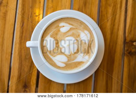 A cup of coffee with a pattern on a wooden table